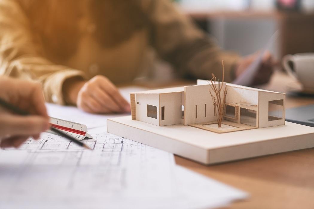 Modellhus og arkitekttegninger, en hånd som tegner i forgrunnen og en person sitter i bakgrunnen.