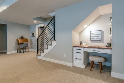 Kjellerstue med blå vegger, trapp og arbeidspult bygd inn i veggen