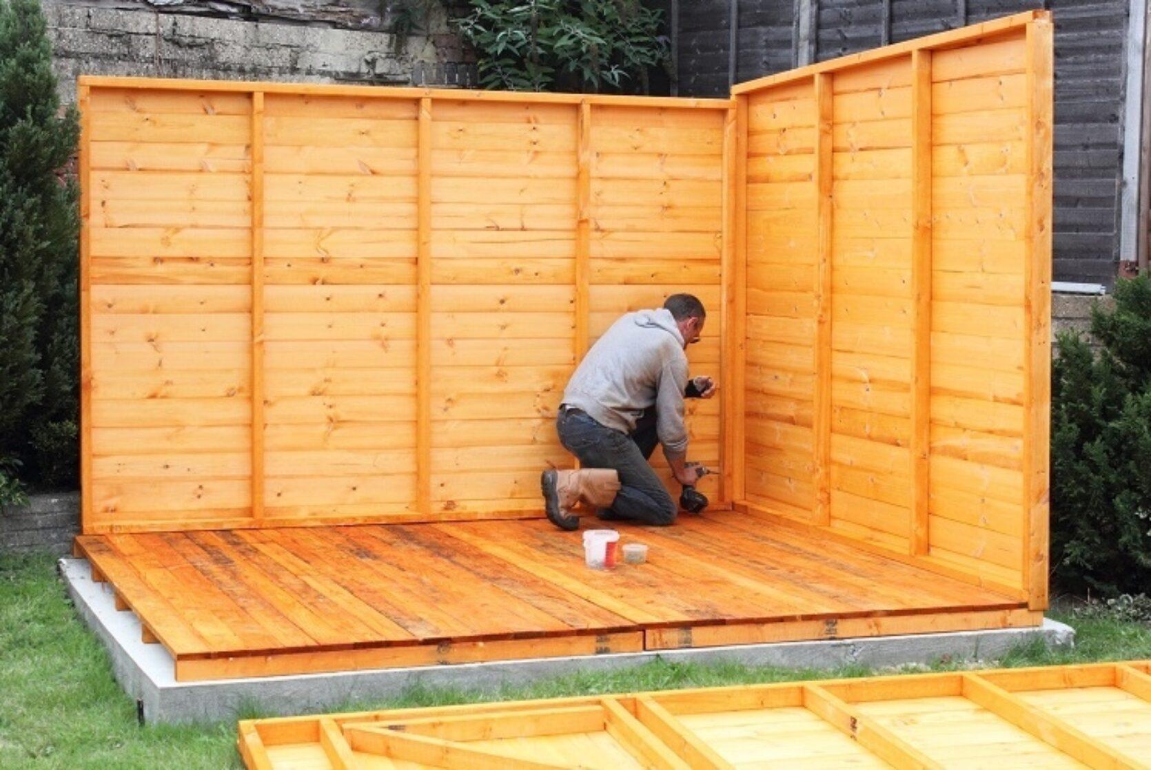 Mann som bygger en utestue, to vegger er satt opp