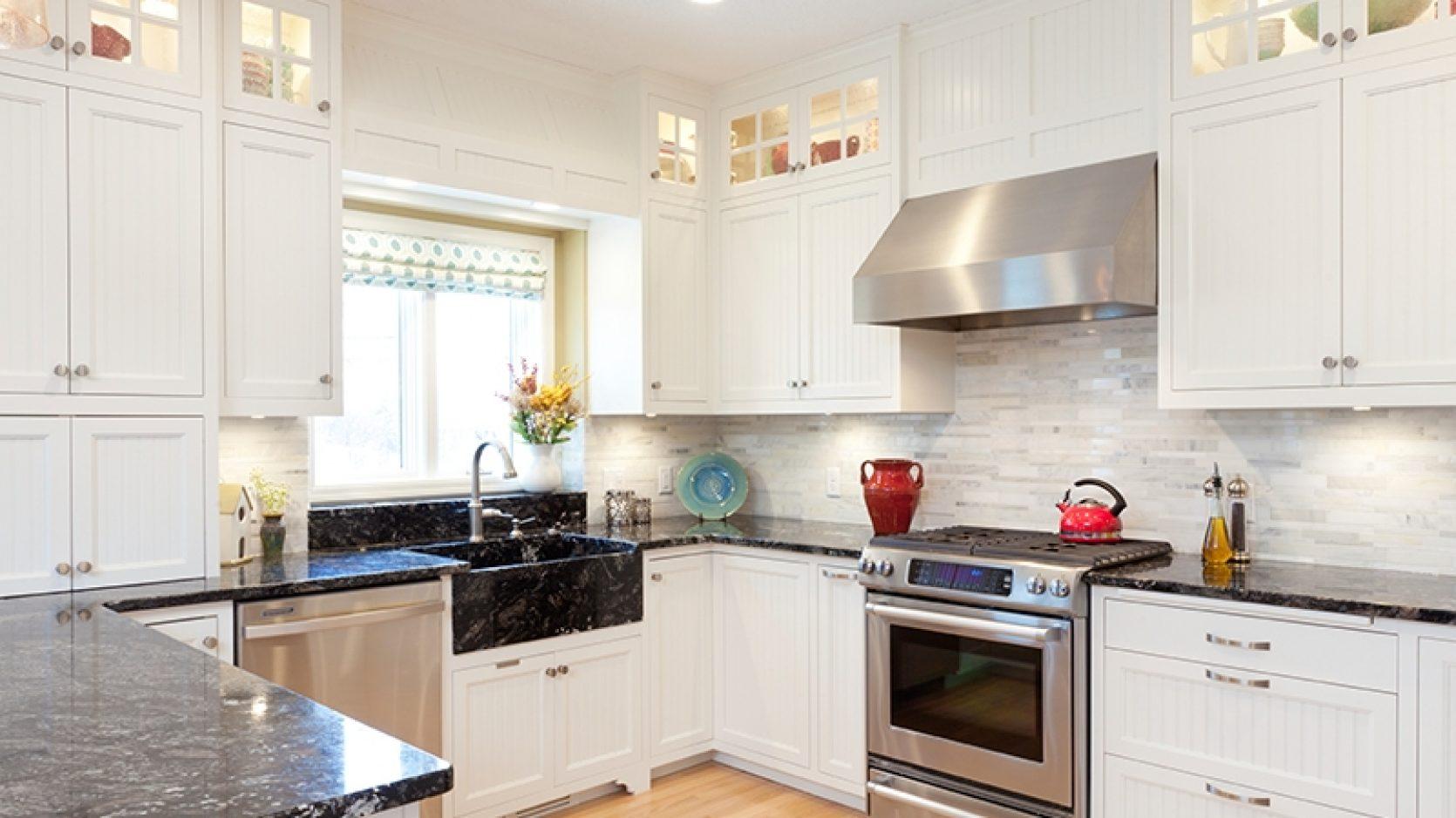 Lyst kjøkken med marmorplater, ovn og vaskemaskin i børstet stål, hvite skap