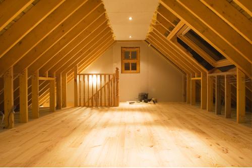 Oppusset loft med skråtak, synlige bærebjelker i taket og treparkett på gulvet