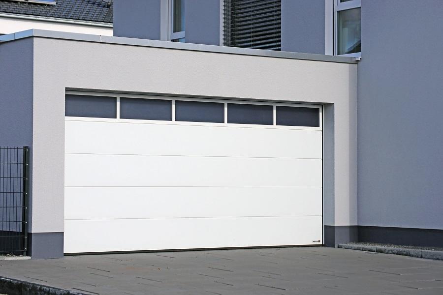 Moderne garasje med bred, hvit port med vinduer øverst