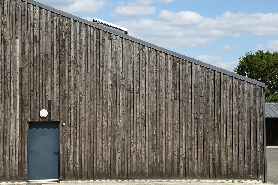 Bygning med skråtak og ubehandlet, stående kledning i mørk, grå trefarge