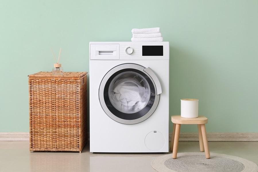 Vaskerom med lyse grønne vegger, hvit vaskemaskin og kurvflettet skittentøyskurv.