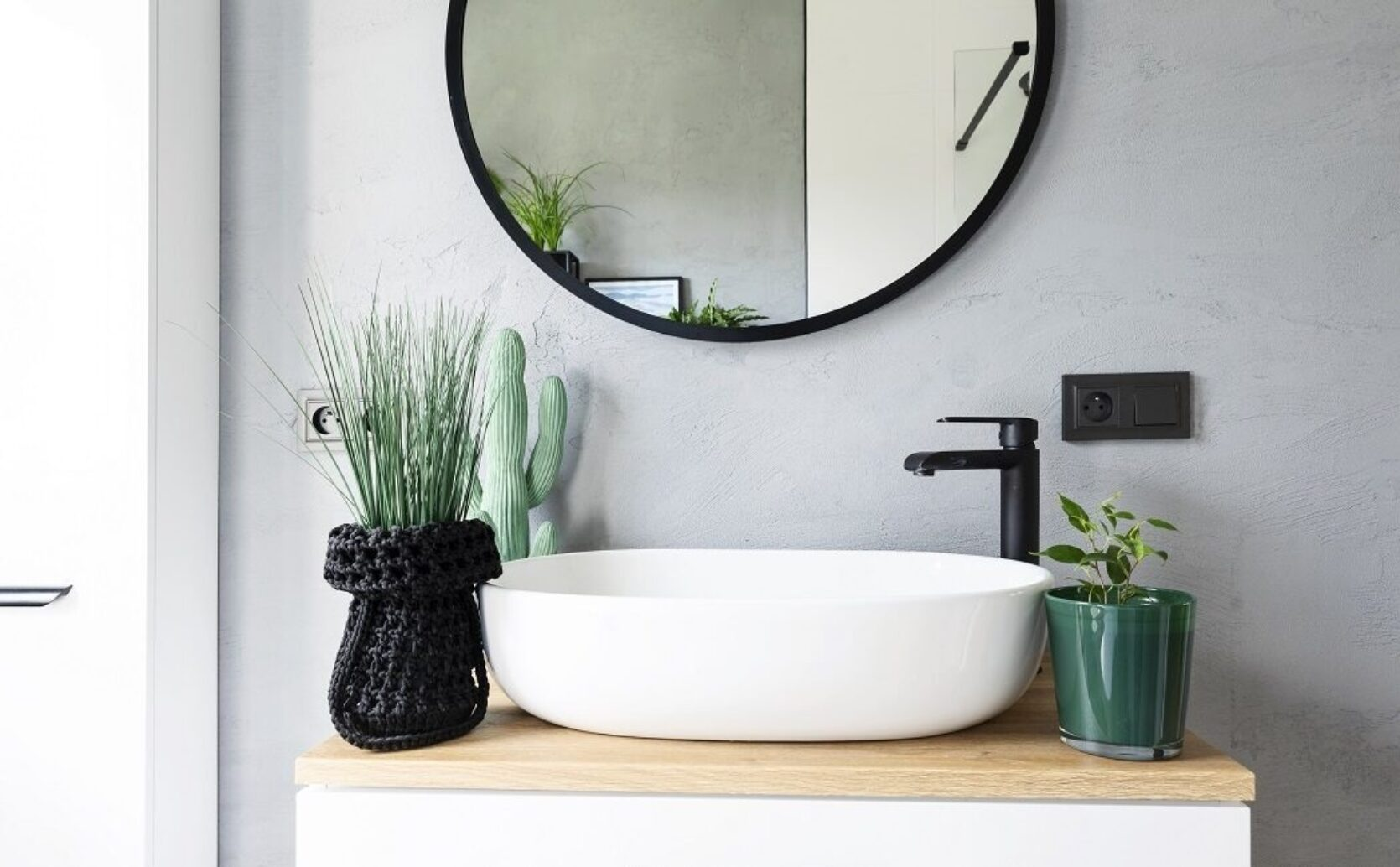 Vask på baderom med sort armatur, grå vegg.