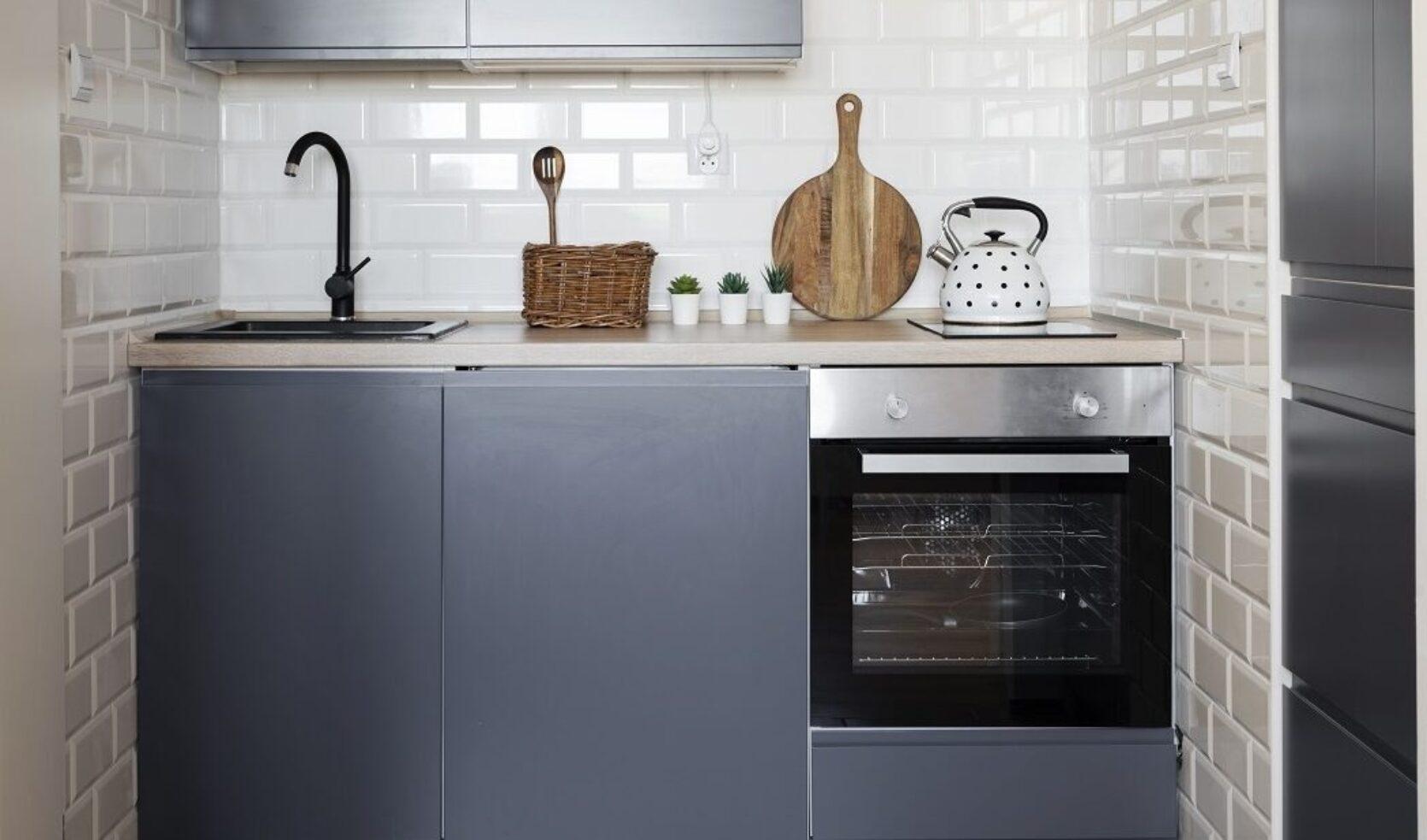 Lite hybelkjøkken med blå skap og hvite fliser på veggen