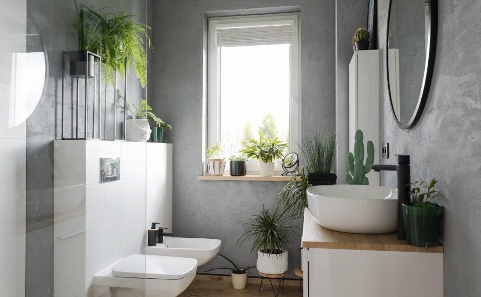 Lite baderom med grå vegger, vindu og hvitt inventar