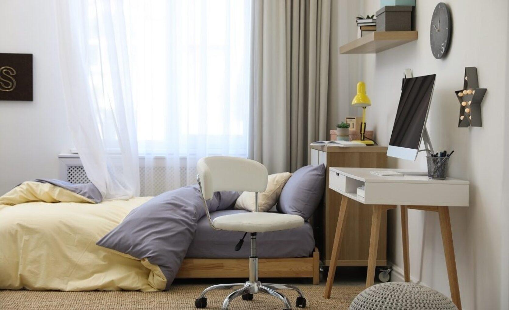 Hybel-soverom med kontorplass, lav seng og lyse farger