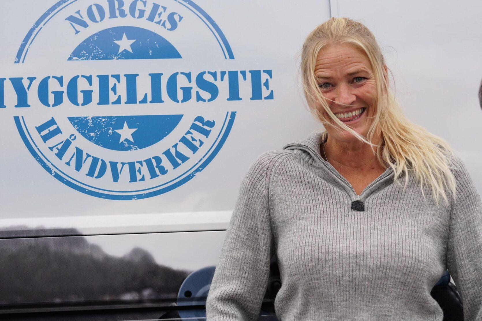 Snekker Linda Jensen foran logoen til Norges Hyggeligste Håndverker