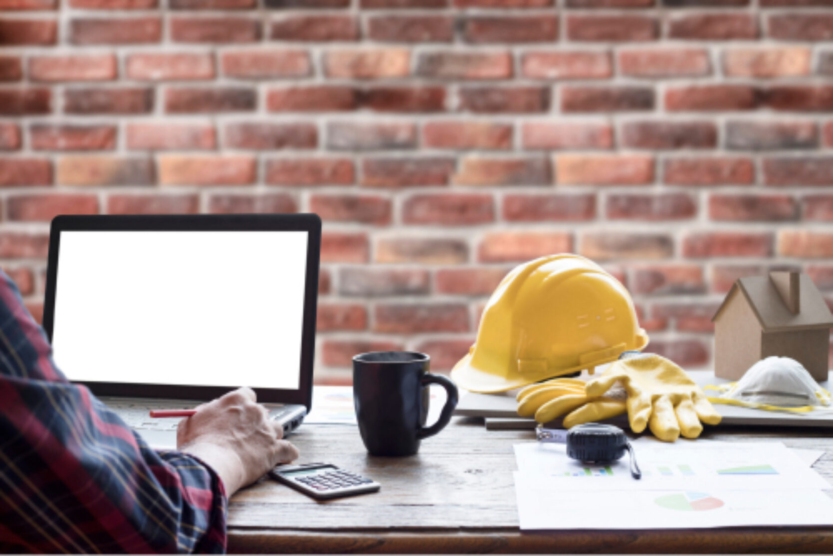 Person som arbeider med laptop, hjelm og arbeidshansker ligger ved siden av