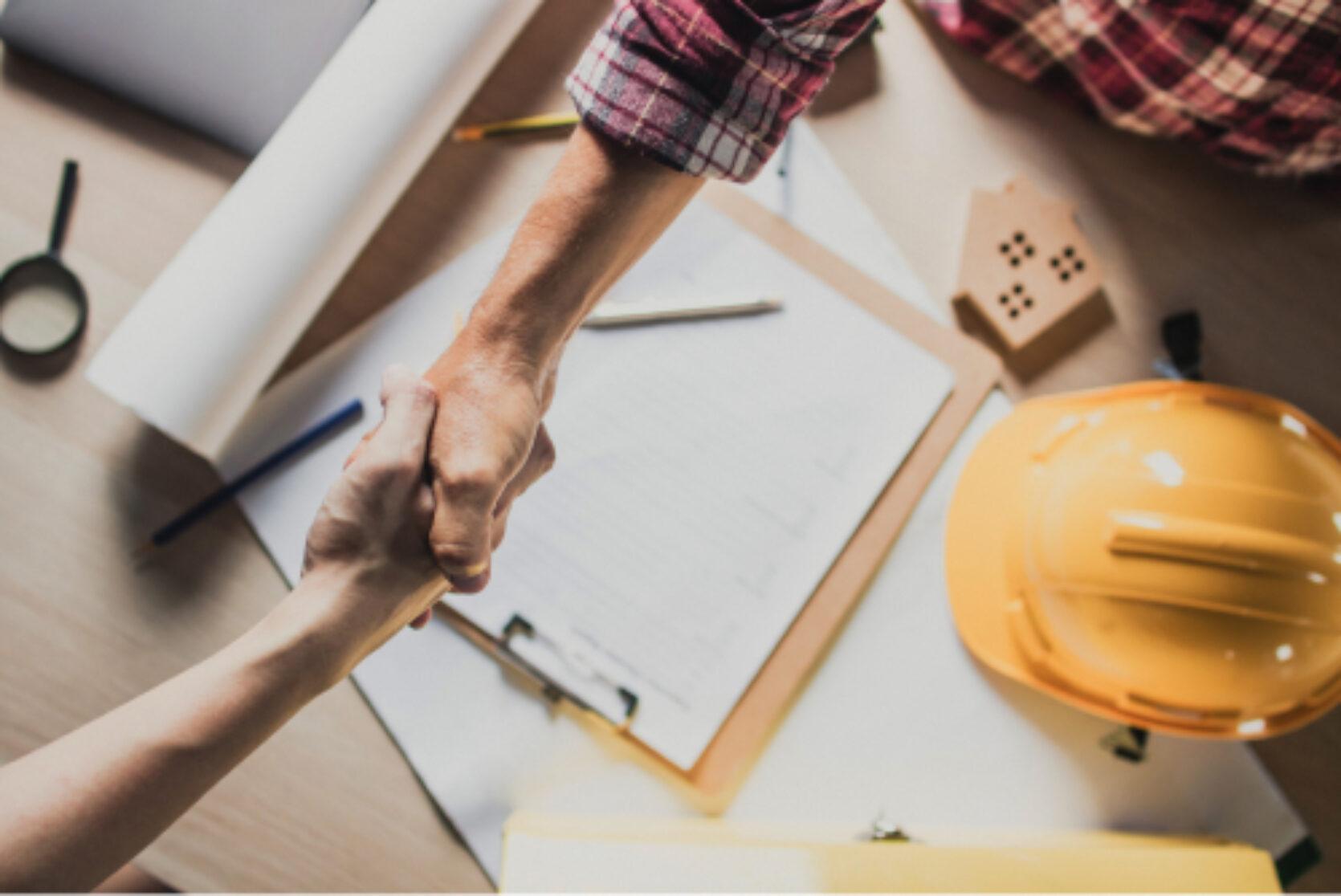 To hender i et håndtrykk sett ovenfra, på bordet under ligger en det en kontrakt for håndverkstjenester og en vernehjelm