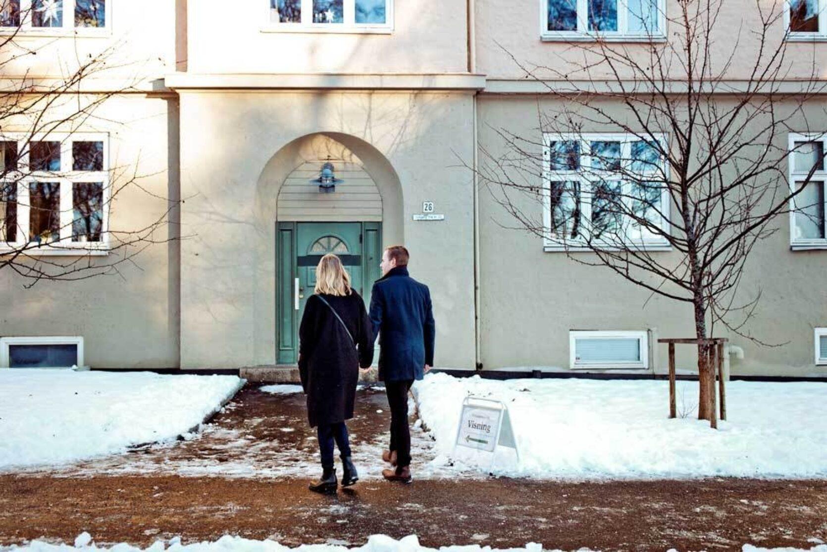 Mann og dame holder hender mens de går inn i en bygård. Det er vinter og snø på bakken