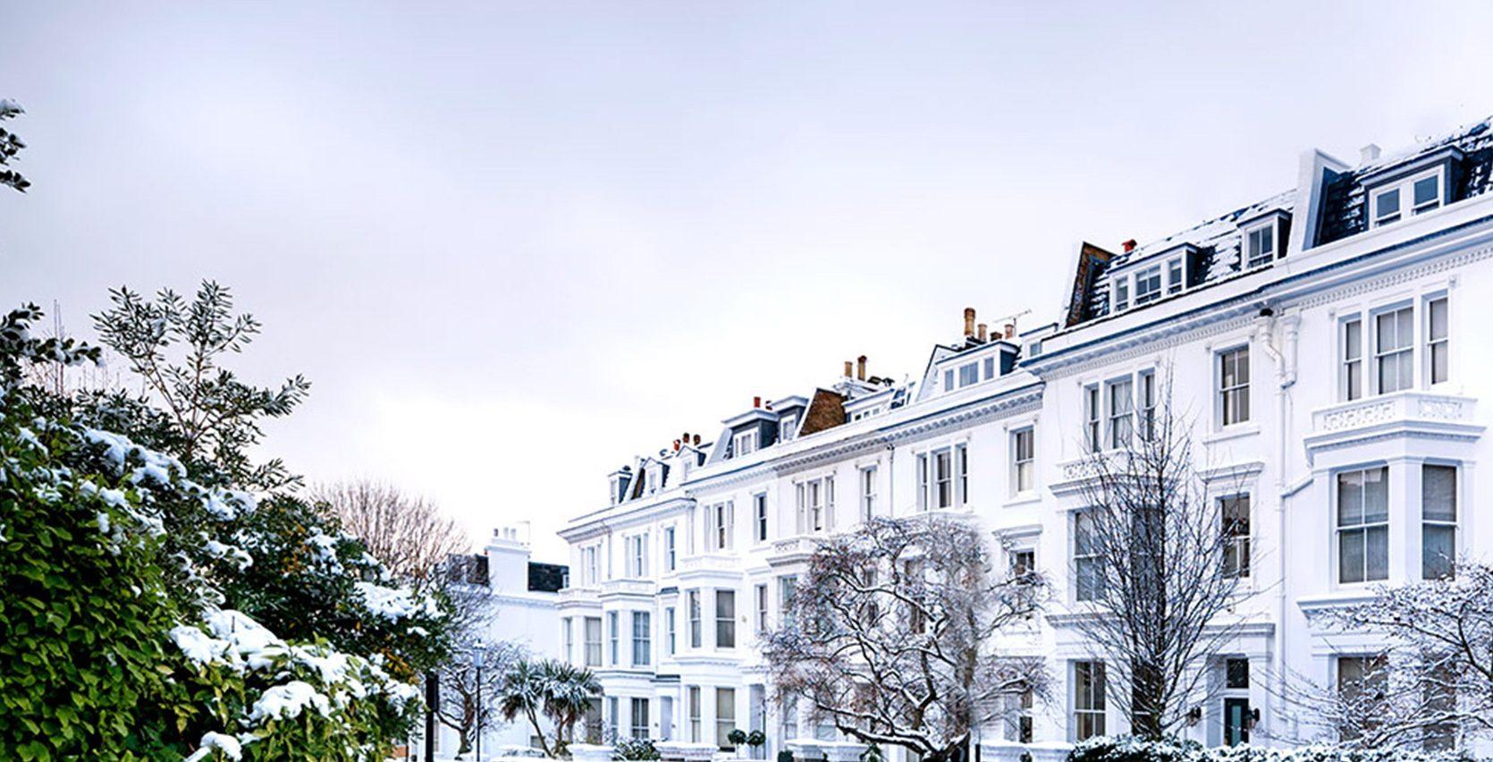 Hvit bygning med flere leiligheter på vinteren