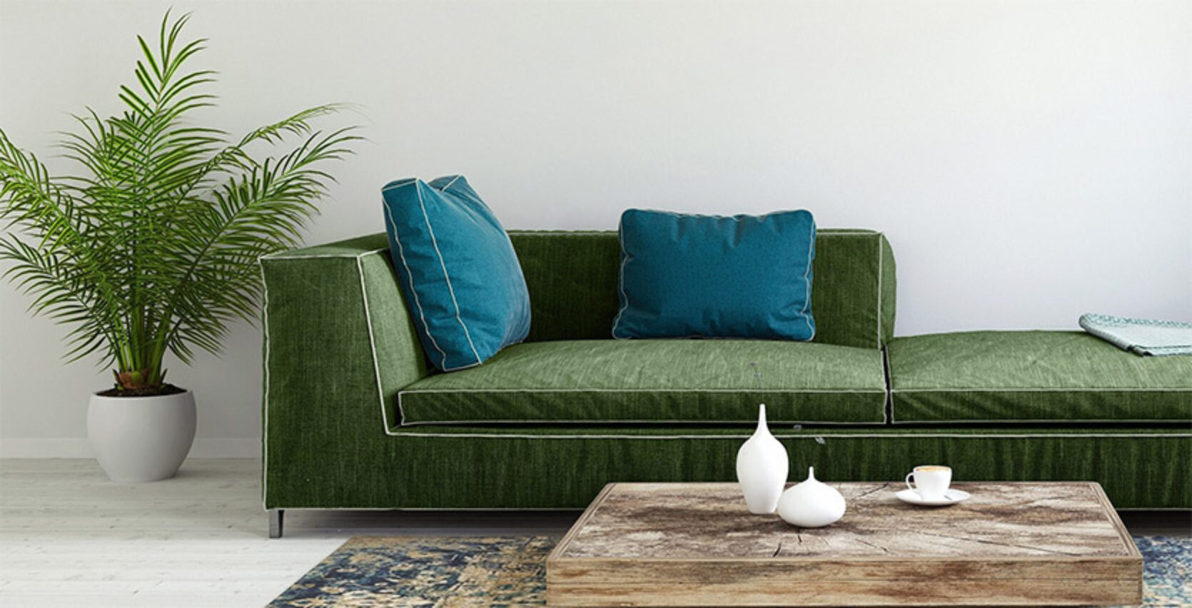 Grønn sofa med blå puter i en stue