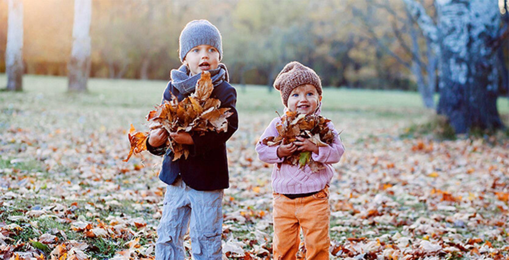 To barn som leker ute i løvet