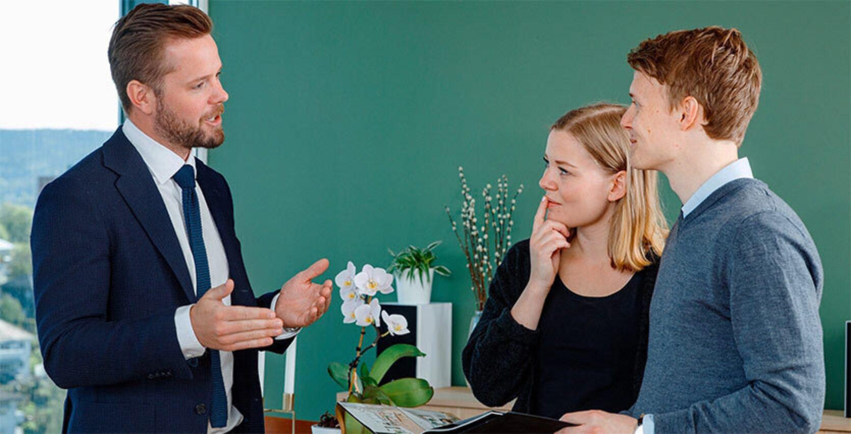 Mann i dress står og prater til to kunder inne i en grønn stue