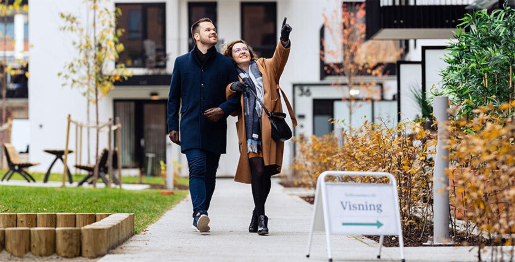 Et par som går ute i høstværet og ser på boliger