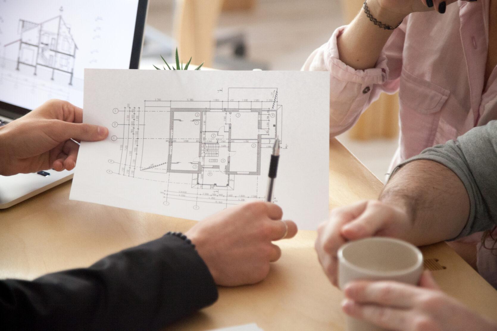 Tre mennesker rundt bord som diskuterer plantegninger for byggeprosjekt