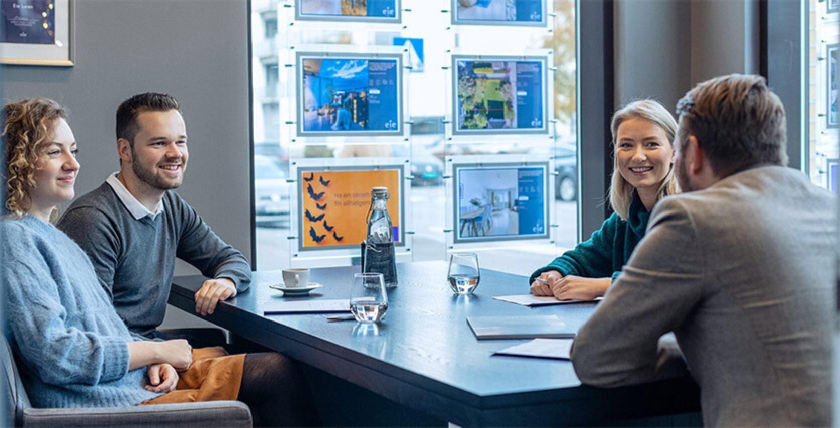 Eiendomsmegler, boligselger- og kjøper sitter rundt et bord og skriver under kontrakter på et meglerkontor