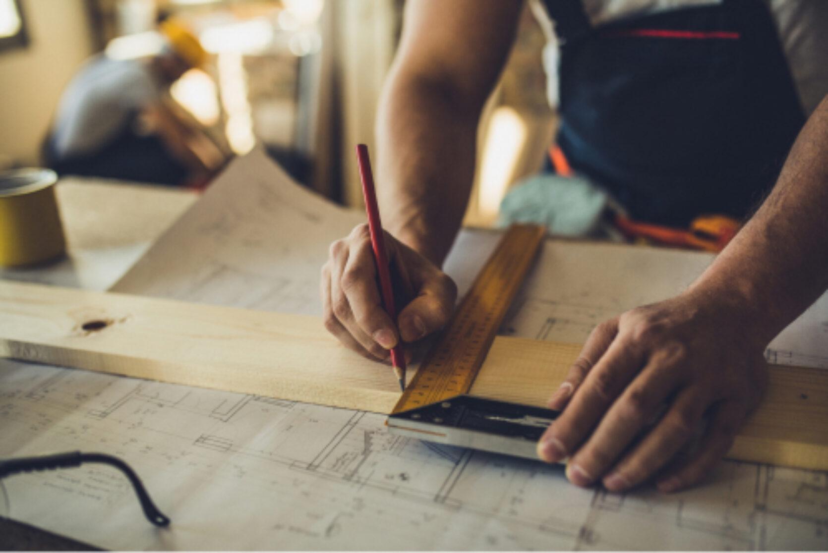 Nærbilde av håndverker som tegner og måler opp med vinkellinjal