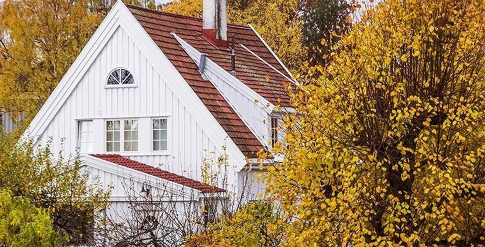 Hvit stor hus med brune taksten som står blant masse trær med brune blader