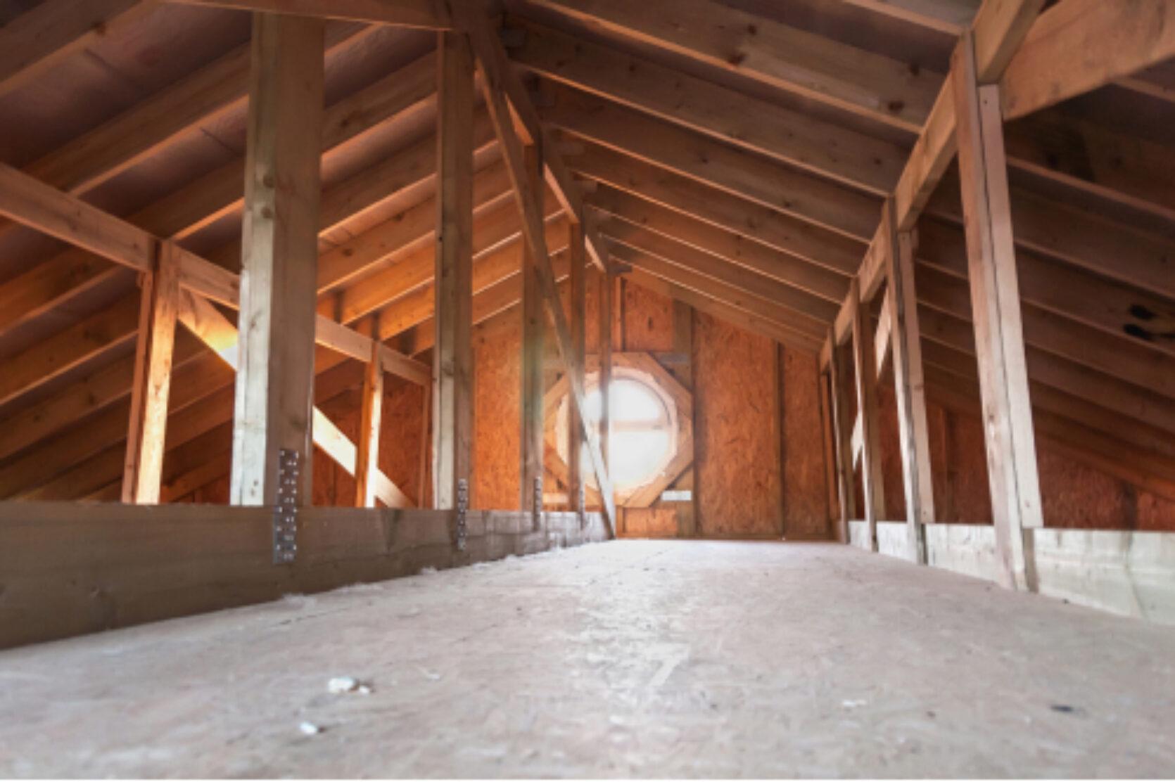 Råloft med synlig stendervek og bærebjelker i taket, uisolert gulv