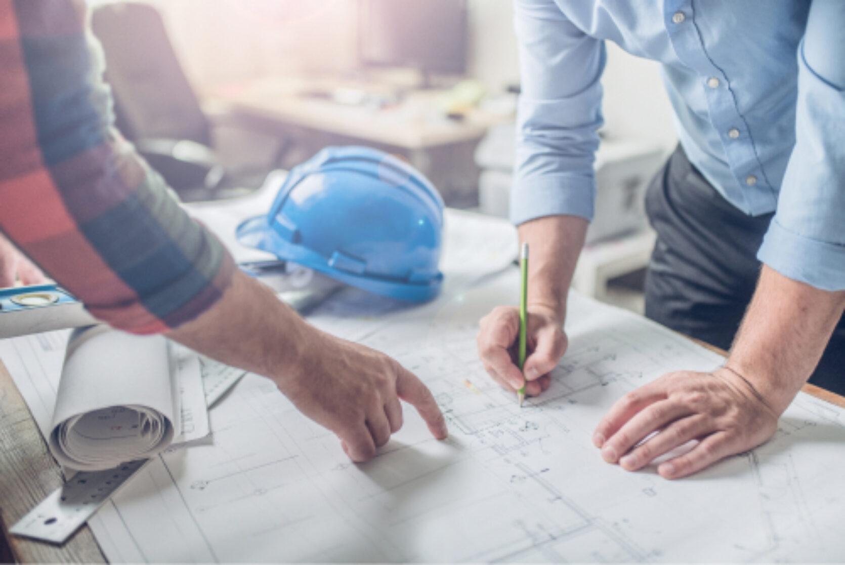 To personer som ser på arbeidstegninger, en av dem peker på skissen mens den andre tegner. En blå arbeidshjelm ligger i bakgrunnen.