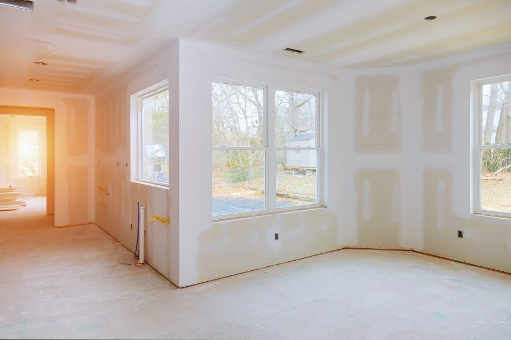 Innendørs i en bolig, umalte veggflater i et nytt tilbygg med store vinduer