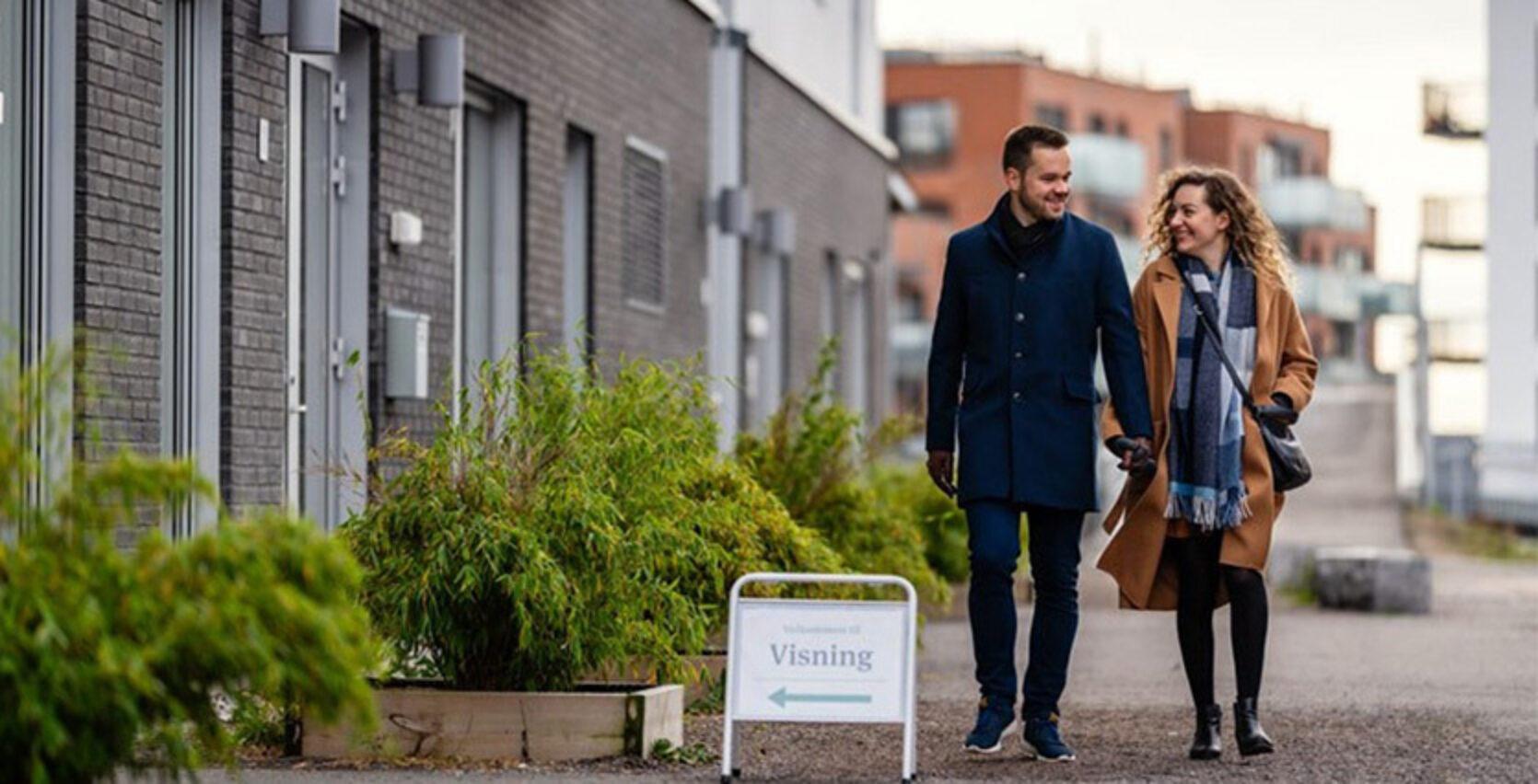 En mann og kvinne går langs en blokk og holder hender på høsten