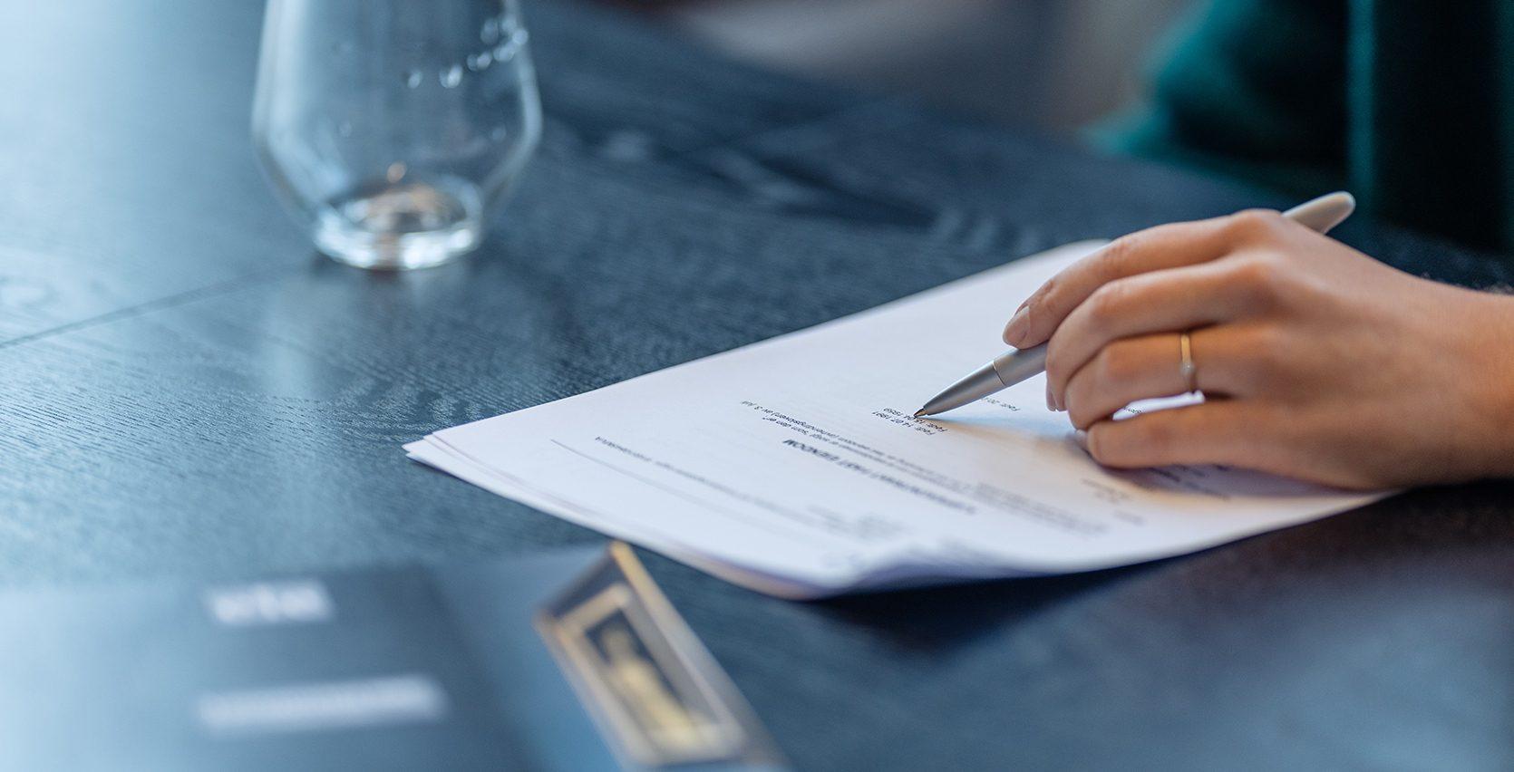 En kvinne som leser og skriver under på en kontrakt
