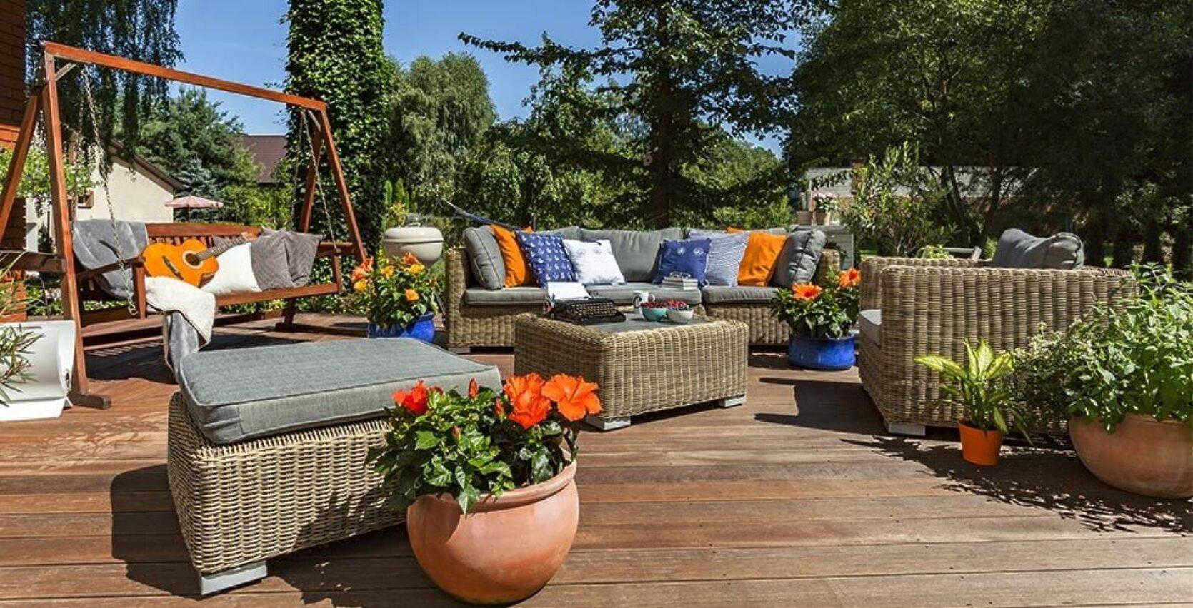 En terrasse i tre om sommeren, med moderne flettede utemøbler og grønne planter i terrakotta.
