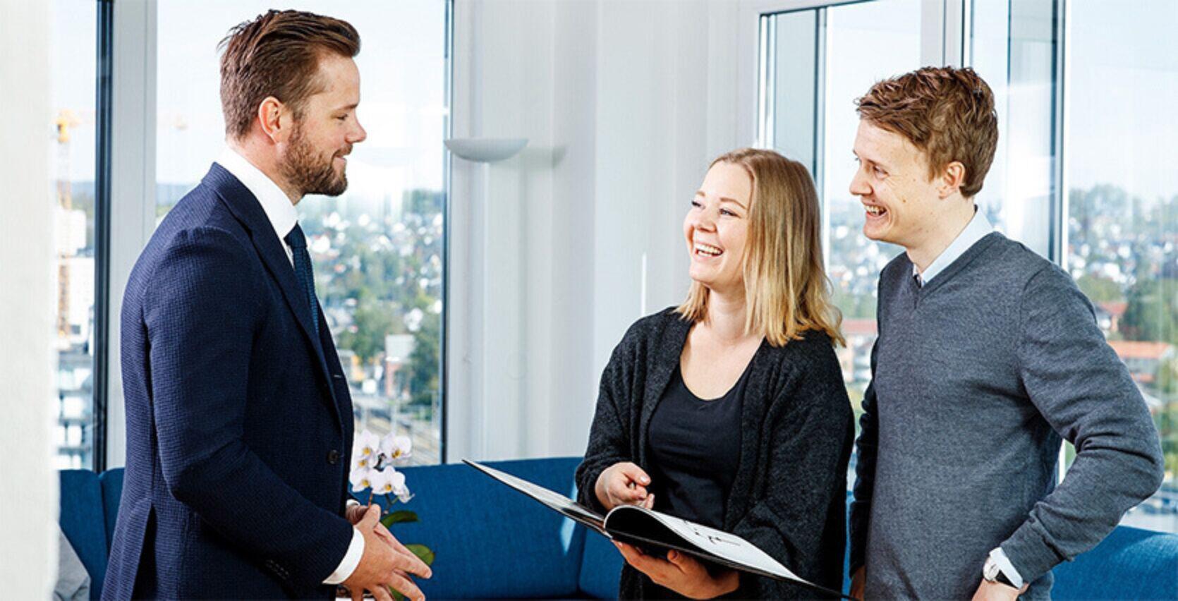 En eiendomsmegler i dress snakker med to kunder inne i en stue med masse vinduer