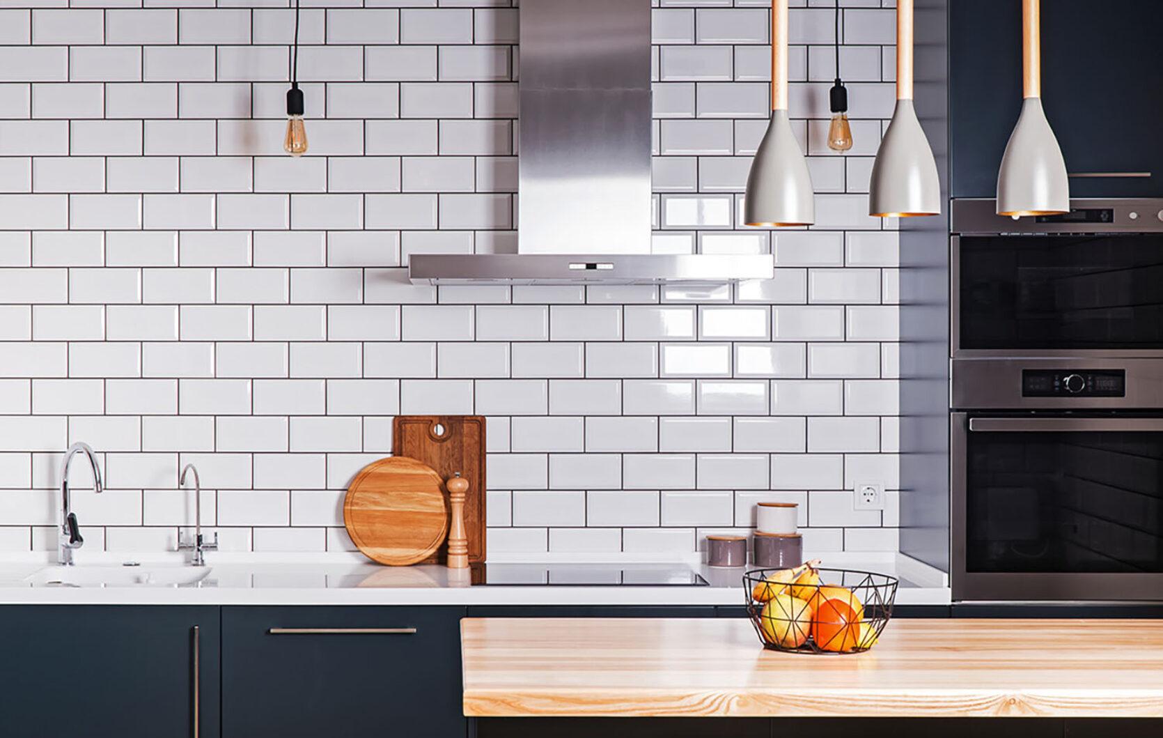 Moderne og stilfullt kjøkken med hvite fliser på veggen, svarte fronter på skap