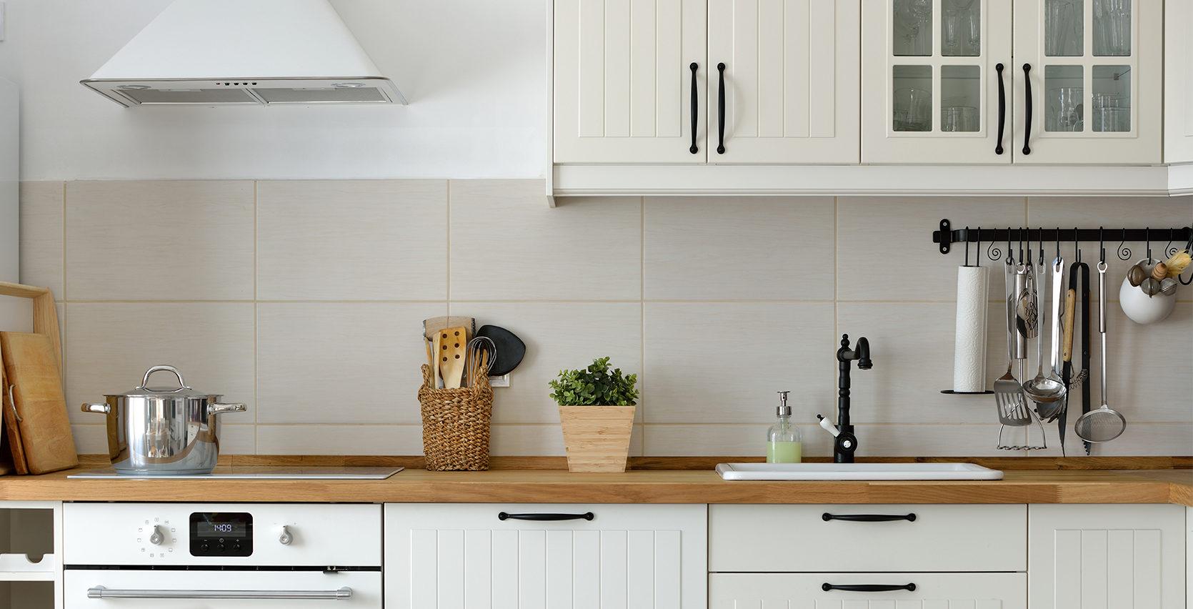 Et hvitt kjøkken med trebenk.