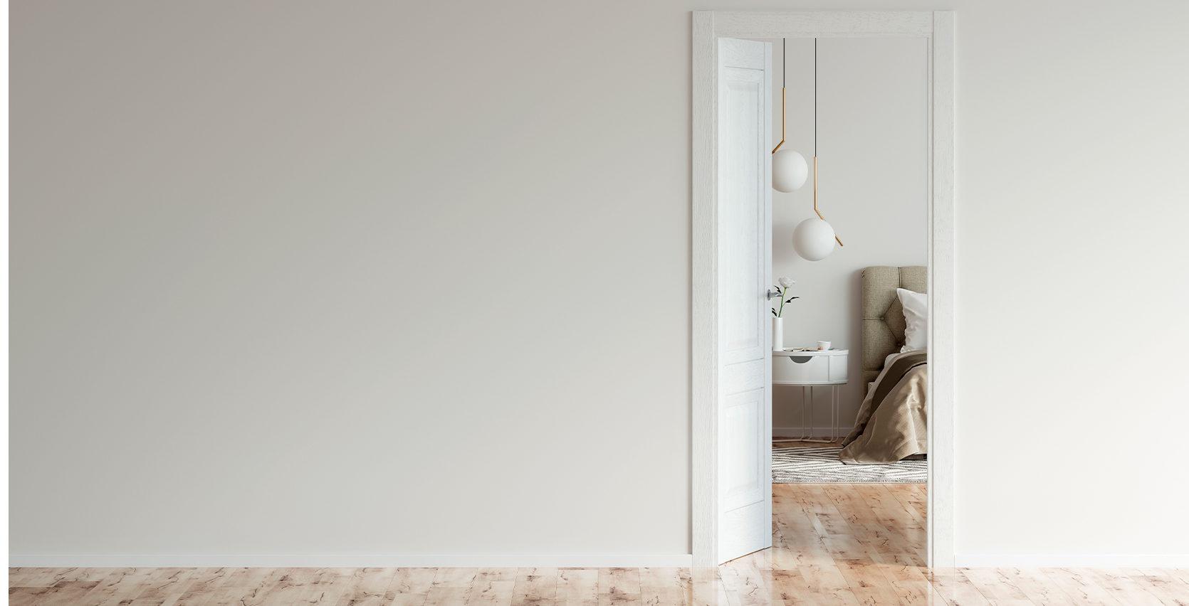 Hvit vegg med en åpen dør som går inn til soverommet