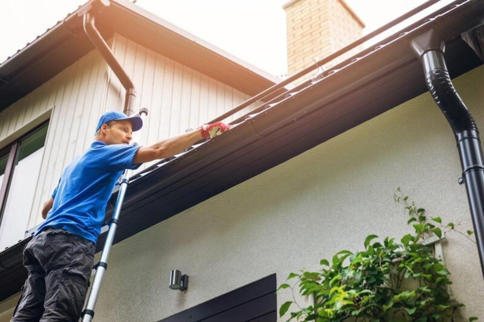 Mann i blå caps og t-skjorte står i stige og renser takrenne på en bolig med hvit kledning.