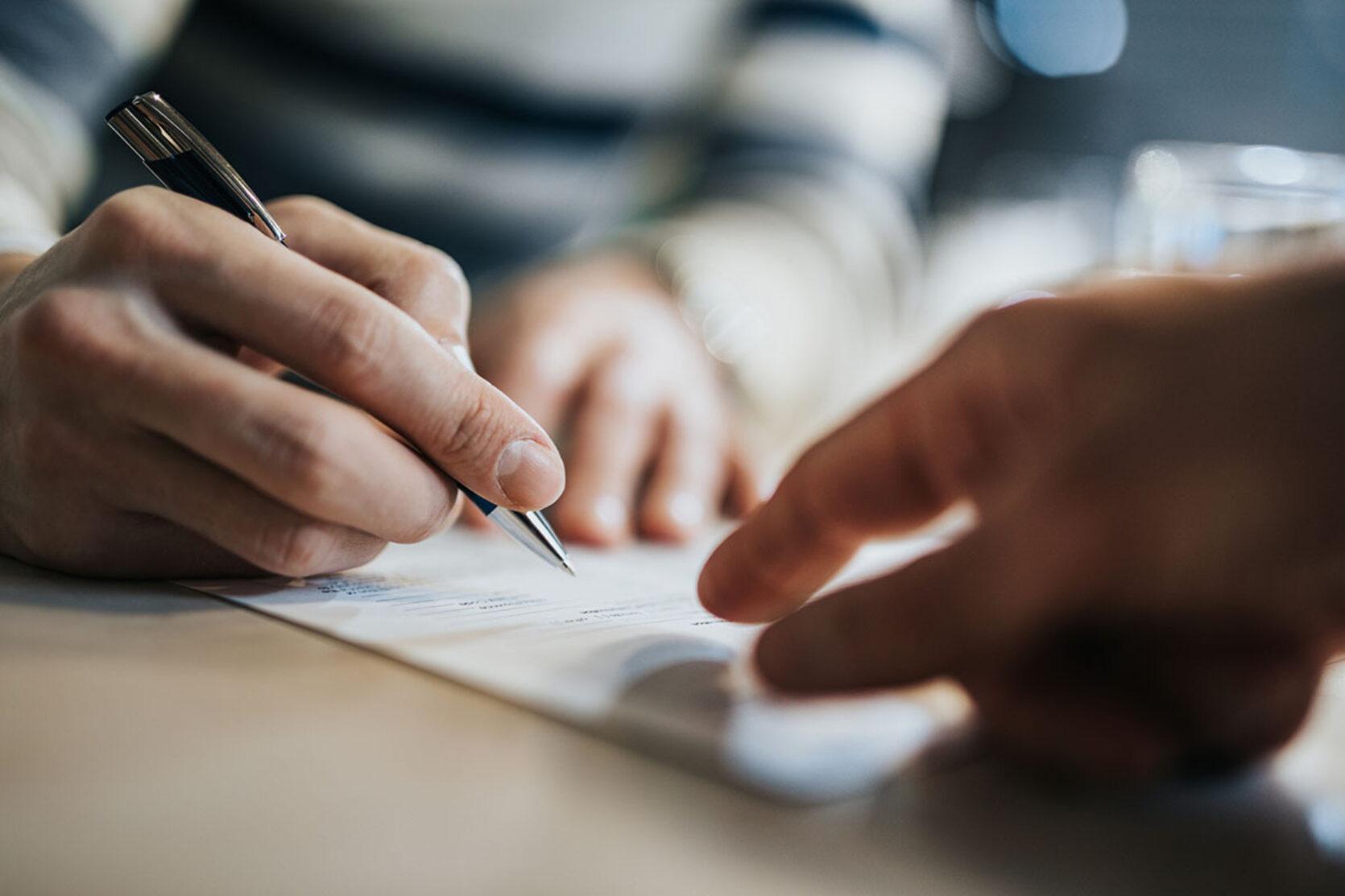 Nærbilde tre hender på et bord med en kontrakt, en skriver under og en peker på dokumentet.
