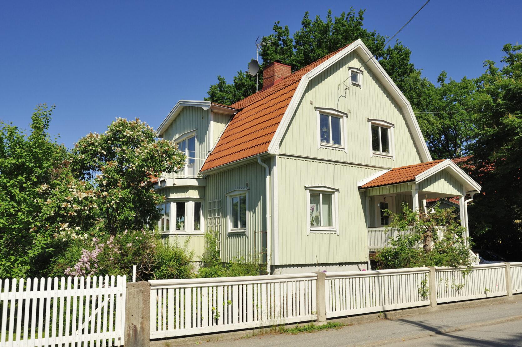 Hus med rød takstein i vakkert sommerlandskap, med hvitt stakittgjerde foran