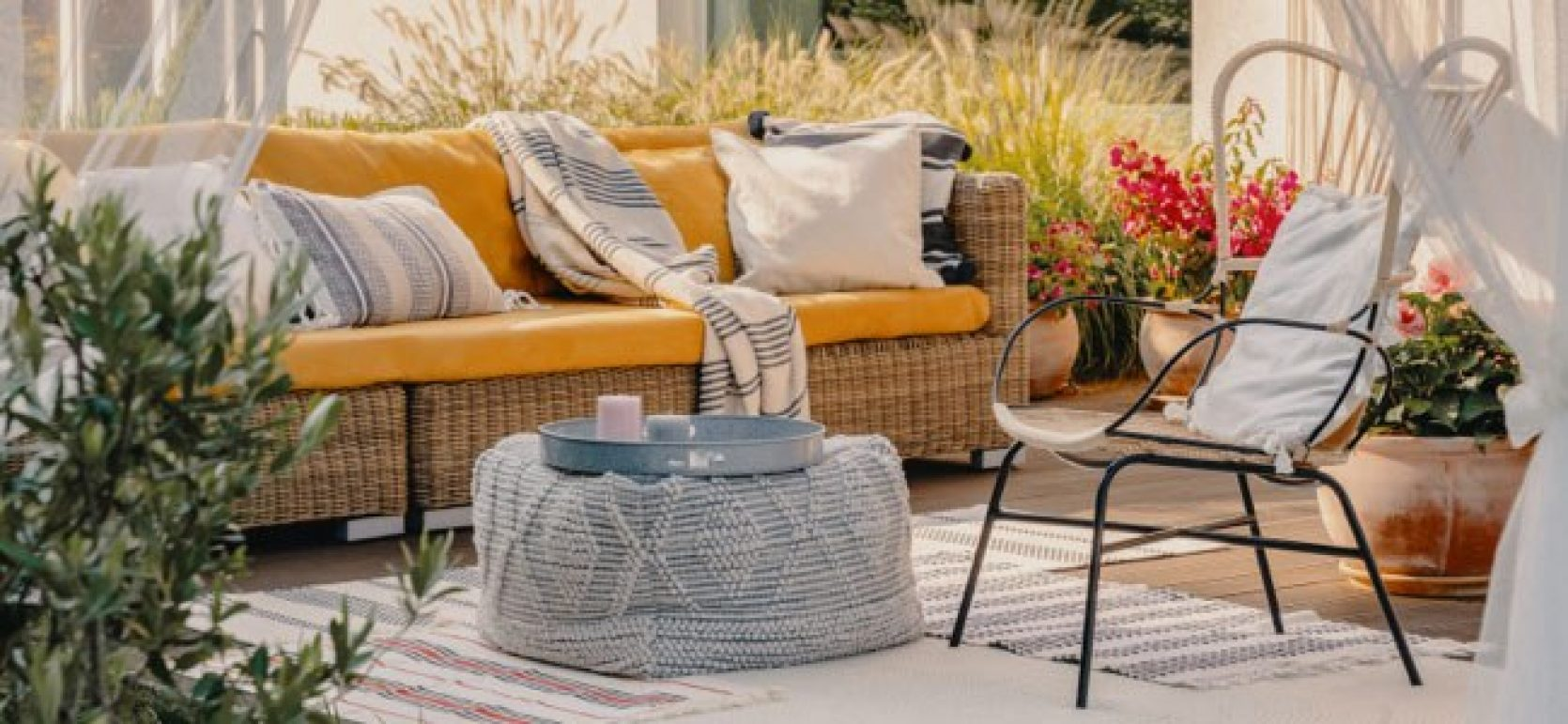 Platting med utemøbler i lyse farger og moderne tekstiler. Beplantning i krukker.