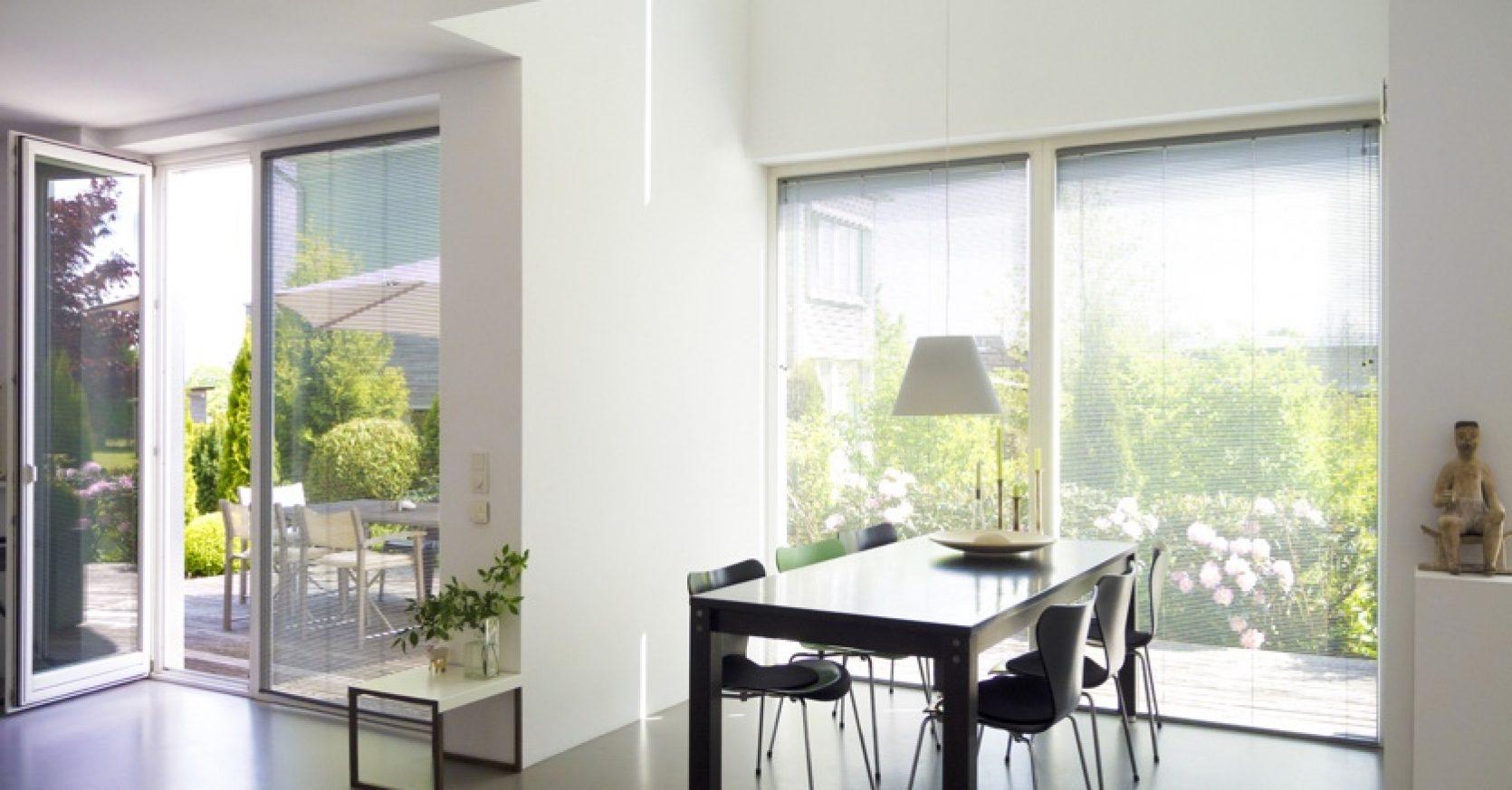 Lyst kjøkken med store vindusflater og balkongdør i glass.