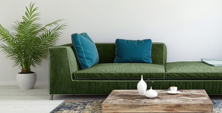 Grønn stue med sofa i fløyel og turkise puter. Pyntet med en palme i hvit potte og et stuebord i drivved.